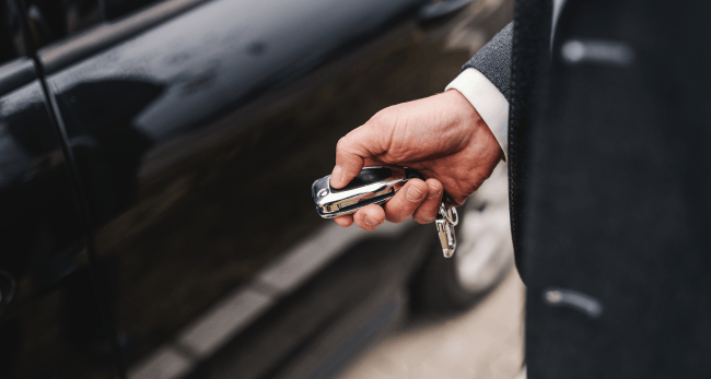 Close up of a man in suit locking his car.