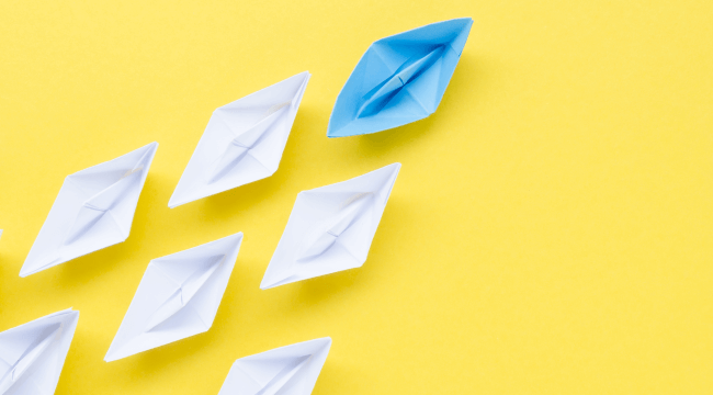 White paper boats with a leading blue boat